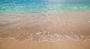 Azurblaue Meereswellen mit Strand mit gelbem Sand Licht des hellen Sonnenscheins und schönes Meer Stockfotografie