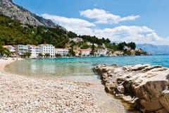 Azurblauer adriatischer Schacht und felsiger Wellenbrecher Stockbilder