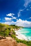 Azurblauer Strand mit felsigen Bergen und klarem Wasser vom Indischen Ozean am sonnigen Tag Lizenzfreies Stockbild
