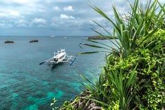 Azurblaues Meer der Ansicht und ein touristisches Boot nahe Grünpflanzen auf kleiner Insel Crystal Coves nahe Boracay-Insel in de lizenzfreies stockfoto
