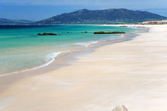 Azure bay near Tarifa and deep blue sky. Azure sea, sand waves on beach and deep blue sky, mediterranean mountains in the background stock photography