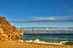Azure beach with stony mountains and clear water of Baikal on a cloudy day. royalty free stock photography