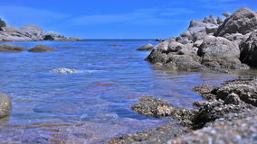 Azure Blue Granite Rock Sea Coast Bay Baia Sardinia Italy. Medium long low angle high dynamic range shallow depth of field tracking slider shot moving towards stock footage
