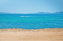 Azure blue seascape with rocks and boat. On a sunny summer day in Mallorca, Spain Stock Images