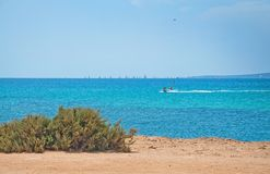 Azure blue seascape with rocks and boat. On a sunny summer day in Mallorca, Spain Royalty Free Stock Photo