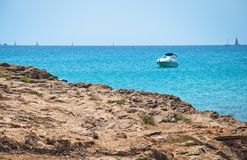 Azure blue seascape with rocks and boat. On a sunny summer day in Mallorca, Spain Stock Image