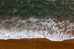Azure clear sea with white waves and orange beach view from top. Stock Photography