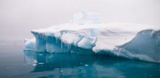 Azure Iceberg - Paradise Bay, Antarctic Peninsula. The still waters around Paradise Bay reflect the blue from icebergs brilliantly Stock Photo