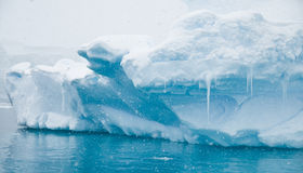 Azure Icebergs and Icicles. An iceberg reflecting it's azure blues in soft snow fall - Antarctic royalty free stock photos