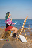 An azure muse. A young girl, an artist, standing on the coast and making a sketch. Volgograd. Volgograd region. Russia. April 4, 2016 Stock Photography