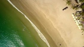Azure ocean waves wash golden beach. Amazing aerial panorama tranquil azure ocean waves wash island golden sand beach with umbrellas and folding chairs in early stock footage