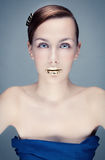 Azure portrait of a young woman with golden lips. Studio photo of a young woman with bright make-up and gold lips Royalty Free Stock Image