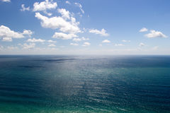 Azure sea water under blue cloudy sky. Aerial view. Horizon at center Royalty Free Stock Photo
