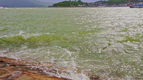 Azure sea waves break at rocky bank against cloudy sky. Panorama azure sea waves with ripple break at brown rocky bank against distant hilly forestry island stock video