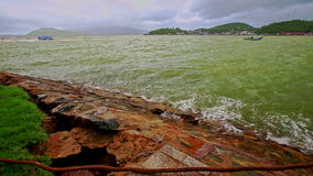 Azure sea waves break at rocky bank against cloudy sky. Panorama azure sea waves with ripple break at rocky bank against distant hilly forestry island cloudy sky stock video