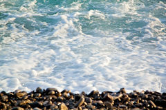 Azure sea waves. Clear blue water with white foam. Pebbles on th Royalty Free Stock Photo
