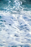 Azure sea waves. Clear blue water with white foam. Pebbles on th Royalty Free Stock Images