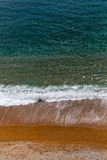 Azure sea with white waves and orange beach view from top. Stock Photo