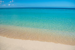 Azure turquoise calm sea, clear blue sky, sandy beach and flat horizon Stock Photo