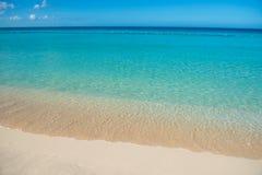 Azure turquoise calm sea, clear blue sky, sandy beach and flat horizon Stock Photo