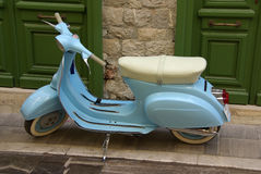 Azure vespa. An azure vespa parked on the pavement stock photography