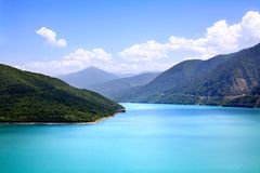Azure water in a blue lagoon among green mountains blue sky white clouds background. Top view stock photography