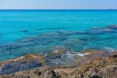 Rocky beach with transparent aquamarine waters on Crete island, Greece. Azure waters of Mediterranean Sea near mountainous Crete island, Greece royalty free stock photography