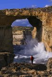 Azure Window, Gozo Island, Malta. Tourist taking in the dramatic view of Azure Window, a natural hole in the coastal cliffs of Gozo Island, Malta Royalty Free Stock Images