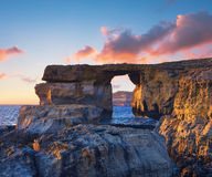 Azure window, natural stone arch by Dwejra cliffs on a sunset. Azure window, natural stone arch by Dwejra cliff, Gozo island, Malta on a sunset. The arch had Stock Photos