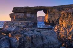 Azure window, natural stone arch by Dwejra cliffs on a sunset. Azure window, natural stone arch by Dwejra cliffs at western Gozo island, Malta, which had Stock Photo