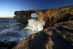 Azure Window at Sunset, Gozo Island, Malta. Waves crashing into Azure Window, a natural hole in the rocky cliffs of Gozo island, Malta Royalty Free Stock Photography