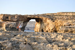 Azure Window. Woman walking on the cliffs near the Azure Window in malta Royalty Free Stock Images