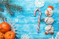 Azure wood background. Green fir tree. Snowman from sweets. Fruit with mandarin. Space for Christmas Message or New Year. stock images