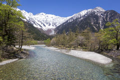 Azusa River and Mountains, Kamikochi, Japan. The cool clear waters of the Azusa River running through the trees at Kamikochi with Japan's Northern Alps in the Stock Images