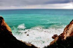 Azuurblauw water tegen de achtergrond van rotsen royalty-vrije stock afbeeldingen