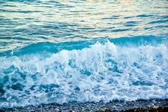 Azuurblauwe overzeese golven Duidelijk blauw water met wit schuim Kiezelstenen op Th Stock Afbeeldingen