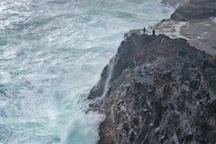 Bøsdalafossur waterfall and high waves against cliffs of the Island Vágar of the Faroe Islands