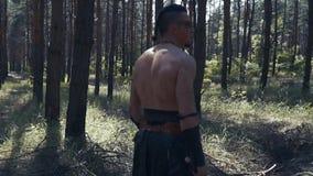 Bárbaro asustadizo con la pintura de guerra en su cara, sosteniendo dos hachas en el bosque almacen de metraje de vídeo