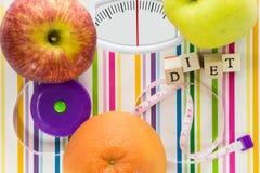 Báscula de baño con las frutas y el texto de la dieta Fotografía de archivo