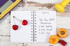 Báscula de baño electrónica y resoluciones del Año Nuevo escritas en cuaderno Fotografía de archivo libre de regalías