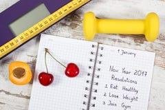 Báscula de baño electrónica y resoluciones del Año Nuevo escritas en cuaderno Fotos de archivo libres de regalías