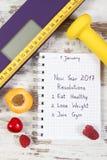 Báscula de baño electrónica y resoluciones del Año Nuevo escritas en cuaderno Fotografía de archivo