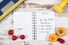 Báscula de baño electrónica y resoluciones del Año Nuevo escritas en cuaderno Imagen de archivo