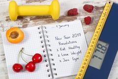 Báscula de baño electrónica y resoluciones del Año Nuevo escritas en cuaderno Imágenes de archivo libres de regalías