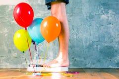 Básculas de baño con los globos coloridos Adelgazar concepto imagen de archivo