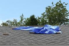Bâche bleue couvrant la fuite résidentielle de toit Photo stock