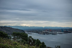 Bâti Rainier Topped With Clouds With le port de Tacoma ci-dessous Photo libre de droits