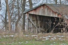 Bâtiment abandonné de ferme dans les bois Photographie stock