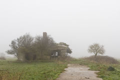 Bâtiment abandonné de ferme dans un jour brumeux Images stock