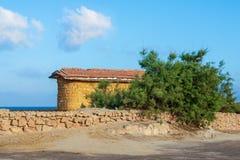 Bâtiment abandonné des briques en pierre et du toit carrelé rouge, arbre de short et barrière verts de pierre sur le fond du ciel Photographie stock libre de droits